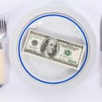 Dollars on food plate — Stock Photo