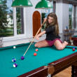 Girl in short skirt playing snooker — Stock Photo