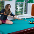 Girl in short skirt playing snooker — Stock Photo #1612712