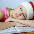 Blonde in red hubcap sleeps on book - Stock Photo