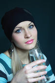 Beautiful blonde keeps glass with water — Stock Photo