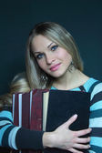 Beautiful blonde in sweater with books — Stock Photo
