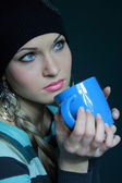 Beautiful blonde in black hat with cup — Stock Photo
