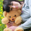 Stock Photo: Girl with plush teddy bear on herb