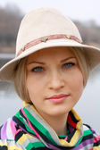 Girl in hat with blue eye near lake — Stock Photo