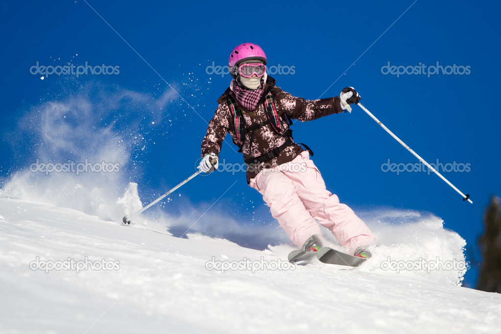 Girl riding on skis with bright blue sky on the background  Stock Photo #1061784