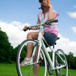 Pretty girl sitting on her bicycle — Stock Photo