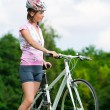 Girl standing with a bicycle — Stock Photo