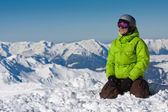 Young man on snow in mountains — Stock Photo