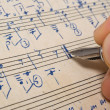 Stock Photo: Hand with pen and music sheet