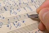 Hand with pen and music sheet — Stockfoto