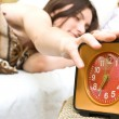 Woman snoozing a red alarm clock — Stock Photo