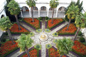 Patio with palm trees and a fountain in the center — Foto Stock