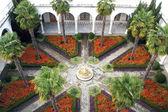 Patio con palmeras y una fuente en el centro — Foto de Stock
