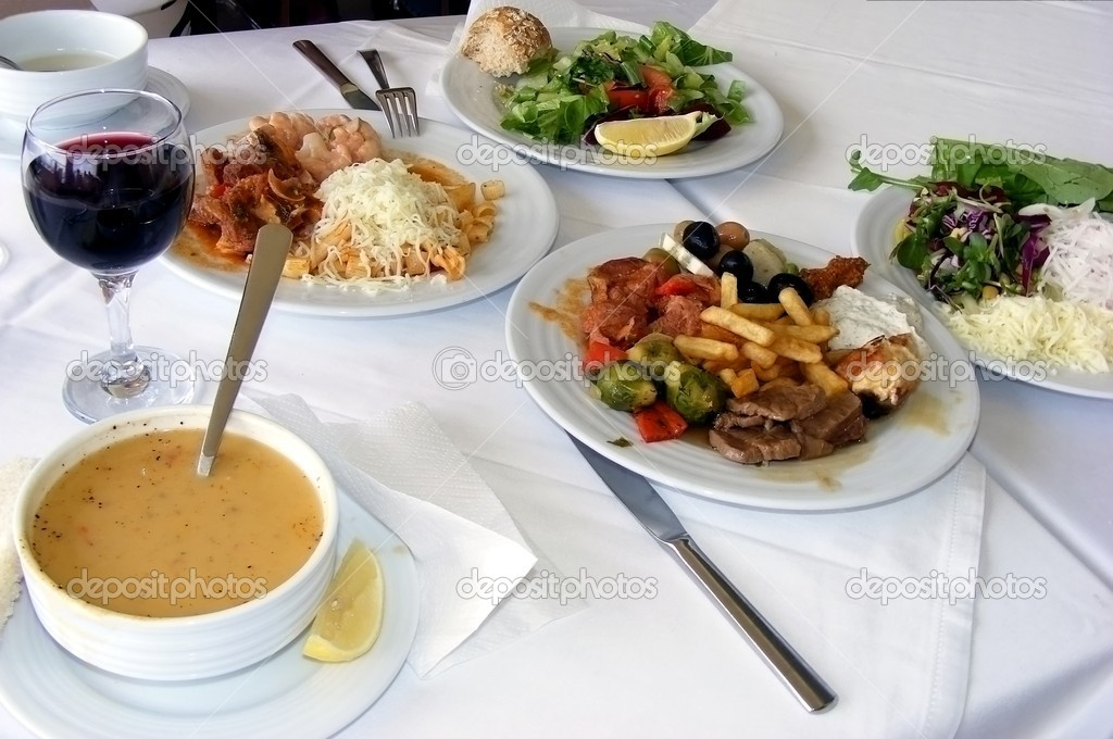 Dinner of several dishes - soup, meat with garnish and salad and wine glass of wine against the white tablecloths — Stock Photo #2203549