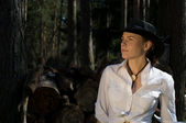 Portrait of a woman in a white shirt and cowboy hat on a ranch. — Stock Photo