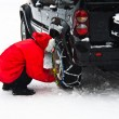 Man installing tire chains - Stock Photo