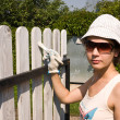 Stock Photo: Beautiful girl colours a wooden fence