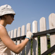 Beautiful girl colours a wooden fence — Stock Photo #1257508