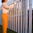 Beautiful girl colours a wooden fence — Stock Photo