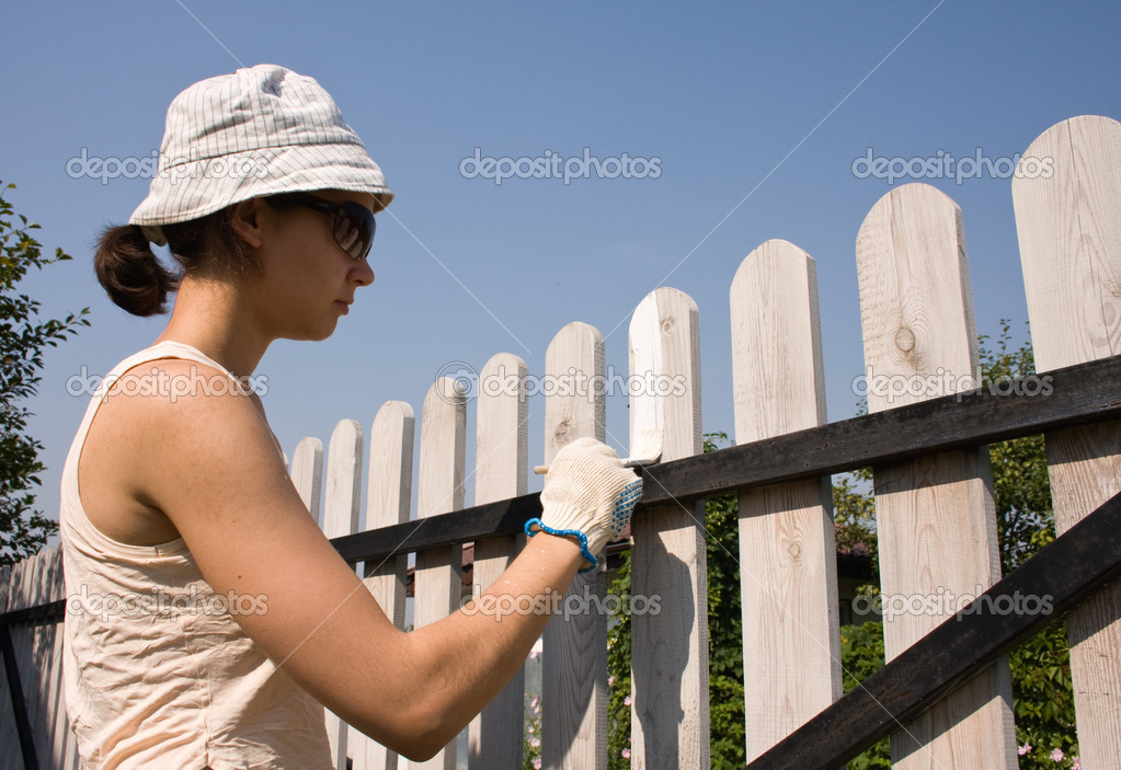   Beautiful girl colours the wooden fence  Stock Photo #1257508