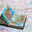 Stock Photo: Big map and small atlas