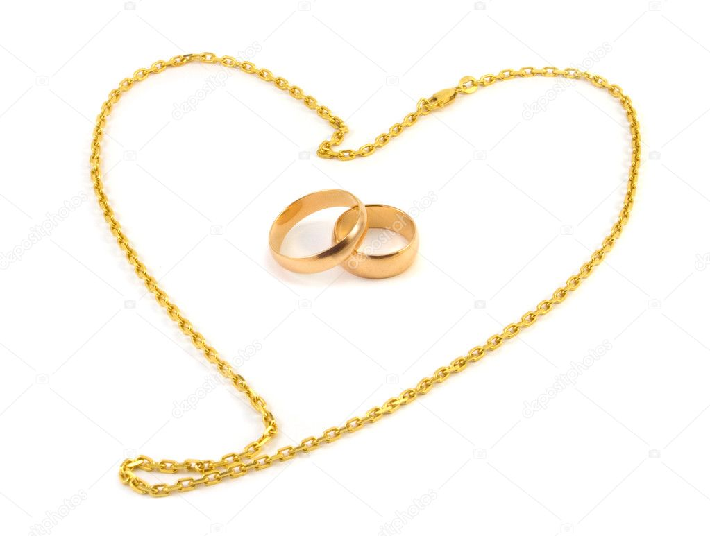 Golden wedding rings with a chain composed of a heart on a white background — Stock Photo #1072767
