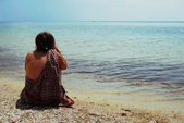 Girl sitting on the seashore and watchin — Stock Photo