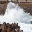 Wave crashing on the breakwater - Stock Photo