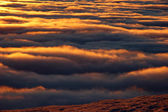 Mountain view of golden clouds at sunset — Stock Photo