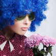 Young beauty clown with flowers — Stockfoto