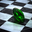 Emerald on a chessboard — Stock Photo