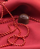 Chocolate and red beads — Stock Photo