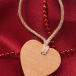 Wooden heart and red beads — Stock Photo #1859095