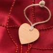 Wooden heart and red beads — Stock Photo