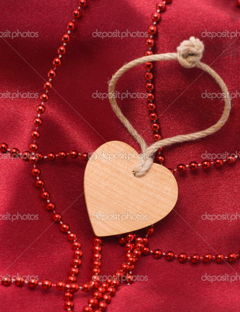 Wooden heart and red beads on a satiny drapery - Souvenir by day of sacred Valentine(Valentin-day) — Stock Photo #1859139