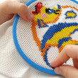 Child hands with embroidery with colorful threads — Stock Photo #1111200