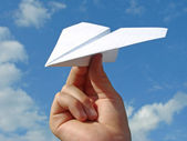 Child hand with paper plane — Stock Photo