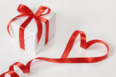 Gift box and red ribbon — Stock Photo