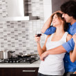 Young couple hug in their kitchen - Stockfoto