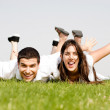 Cute young Couple lie down on grass — Stock Photo