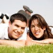 Happy young Couple lie down on grass — Stock Photo #1142588