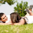 Happy young Couple lie down on grass — Stock Photo #1142613