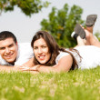 Beautiful young Couple lie down on grass — Stock Photo