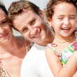 Kid and parents smiling in the beach - Stock Photo