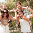 Children sitting on parents shoulders — Stock Photo #1147495
