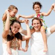 Children sitting on parents shoulders — Stock Photo #1147519