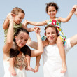 Children sitting on parents shoulders — Stock Photo