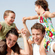 Children sitting on parents shoulders - Stockfoto