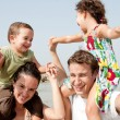 Children sitting on parents shoulders - Stock Photo